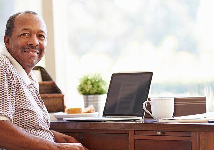 Senior Man Using Laptop On Desk At Home